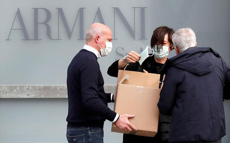 A worker holds a face mask outside the theatre where the Italian designer Giorgio Armani said his Milan Fashion Week show would take place in Milan - REUTERS