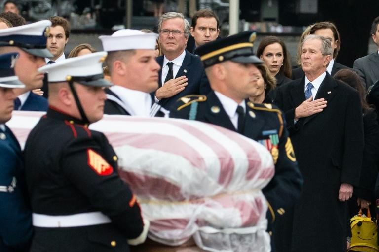 Former US president George W. Bush and brother Jeb Bush wait as the casket of their father, former US president George W.H. Bush, is carried upon arrival at his presidential library center