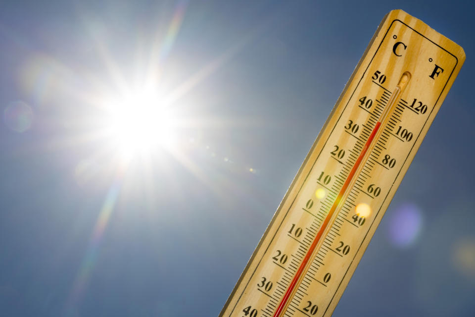 Mercury thermometer marking 39 degrees Celsius 100 Fahrenheit in a sunny day. Summer heat shown on mercury thermometer against the blue sky. Sunlight with sun flares.