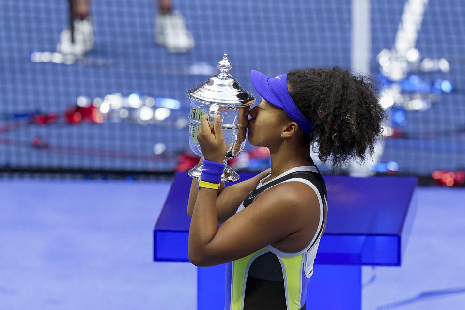 FILE - Naomi Osaka, of Japan, holds up the championship trophy after defeating Victoria Azarenka, of Belarus, in the women's singles final of the U.S. Open tennis championships in New York, in this Saturday, Sept. 12, 2020, file photo. The two singles champions at this year's U.S. Open each will earn 35% less than in 2019, the last time the Grand Slam tennis tournament allowed spectators, while prize money for qualifying and the first three rounds of the main draw will rise as part of an overall increase. A year after banning fans entirely during the coronavirus pandemic and lowering prize money because of lost revenue, the U.S. Tennis Association announced Monday, Aug. 23, 2021, that it will be boosting total player compensation to a record $57.5 million, slightly more than the $57.2 million in 2019. (AP Photo/Seth Wenig, File)
