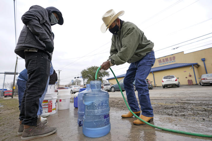 Leovardo Perez, right, fills a water jug using a hose from a public park water spigot Thursday, Feb. 18, 2021, in Houston. Texas officials have ordered 7 million people to boil tap water before drinking it following days of record low temperatures that damaged infrastructure and froze pipes.(AP Photo/David J. Phillip)