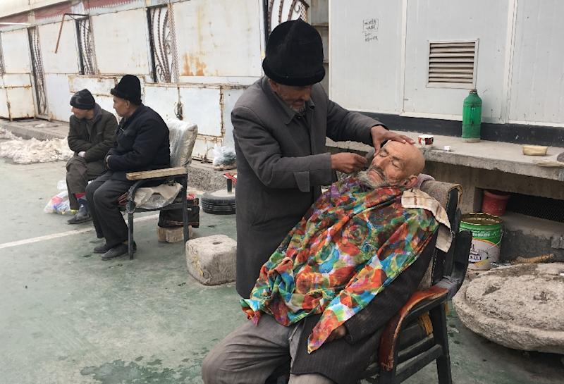 A barber shaves a man outside of a mosque in Kashgar, in China's western Xinjiang region which one of the most policed places on earth (AFP Photo/BEN DOOLEY)