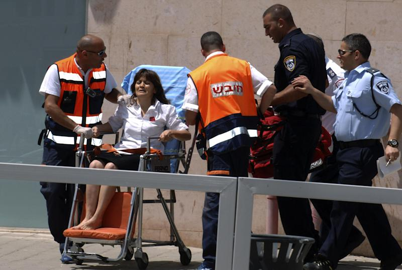An Israeli woman is taken out of a bank in the town of Beersheba, Monday, May 20, 2013. A gunman stormed into a bank in the southern Israeli city of Beersheba Monday, killing four people in a gunfight and taking a hostage before killing himself, police said. (AP Photo/Dudu Greenspan) ***ISRAEL OUT***