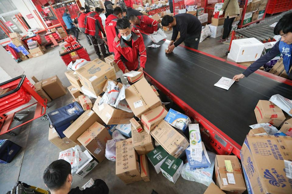 Workers sort out packages for delivery at a JD.com delivery station in Beijing, China, on November 11, 2020. Photo: Simon Song
