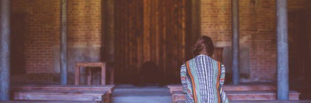 back of a woman sitting at a church alone in a pew