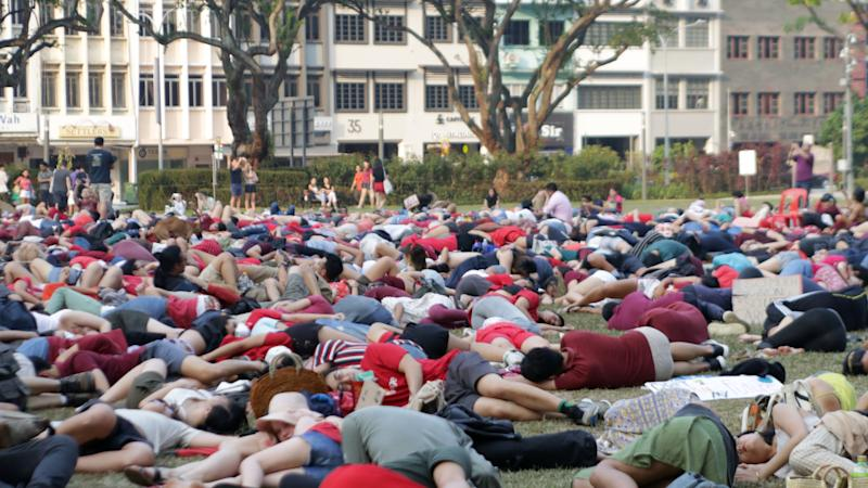 """SG Climate Rally attendees stage a """"die-in"""" to symbolise the loss of human life and biodiversity due to climate change at Hong Lim Park on Saturday (21 September). (PHOTO: SG Climate Rally)"""