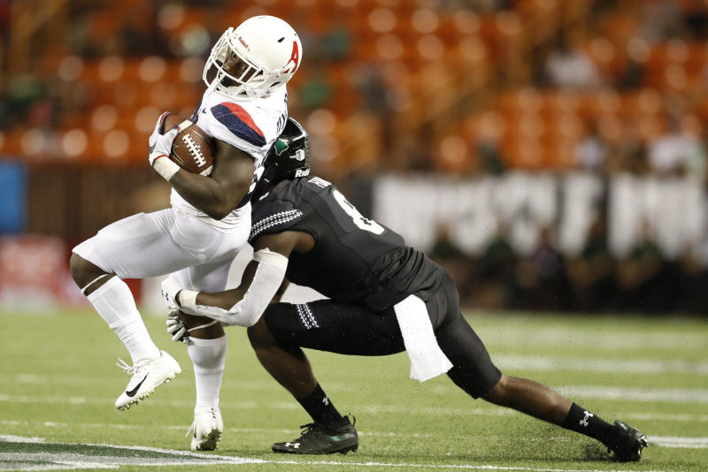 Arizona running back J.J. Taylor (21) tries to get around Hawaii defensive back Eugene Ford (8) in the second half of an NCAA college football game, Saturday, Aug. 24, 2019, in Honolulu. (AP Photo/Marco Garcia)