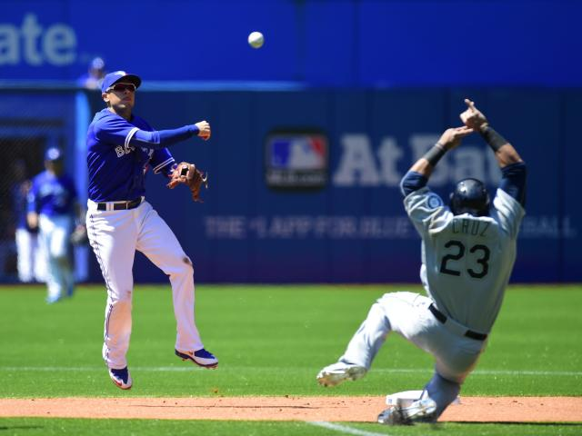 Toronto Blue Jays shortstop Ryan Goins turns a double play as Seattle Mariners' Nelson Cruz slides late into second during the sixth inning of a baseball game Saturday, May 23, 2015, in Toronto. (Frank Gunn/The Canadian Press via AP) MANDATORY CREDIT