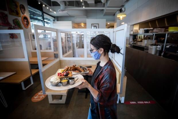 A server brings a food order to indoor diners at a Yolks restaurant in Vancouver on Tuesday. British Columbians can once again enjoy an indoor restaurant meal after the province laid out a roadmap for reopening. (Ben Nelms/CBC - image credit)