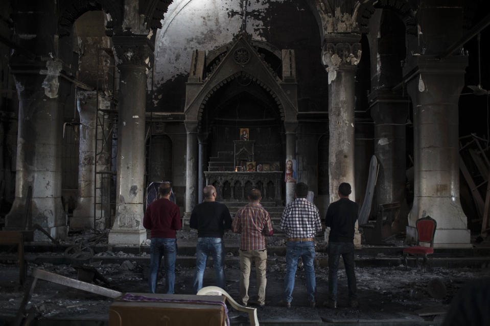 FILE - In this Nov. 12, 2016 file photo, Iraqi Christians pray at the Church of the Immaculate Conception, damaged by Islamic State fighters during their occupation of Qaraqosh, east of Mosul, Iraq. Pope Francis is pushing ahead with the first papal trip to Iraq despite rising coronavirus infections, hoping to encourage the country's dwindling number of Christians who were violently persecuted during the Islamic State insurgency while seeking to boost ties with the Shiite Muslim world. (AP Photo/Felipe Dana)