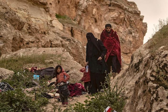 Surrendering Islamic State group jihadists and their families flee through the arid hills around their last redoubt in biblical scenes that intensified daily (AFP Photo/Delil souleiman)