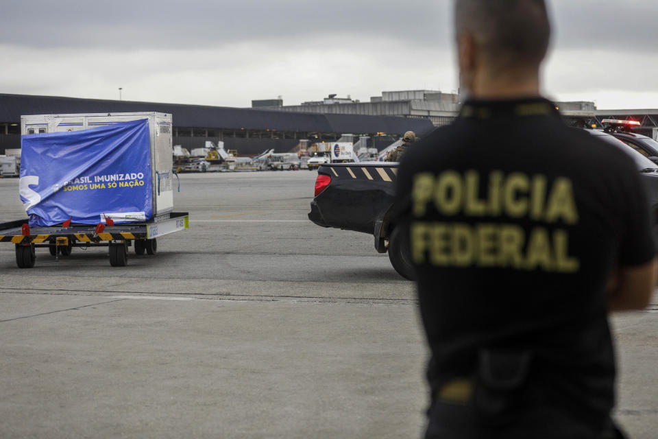 Federal police watch a container of vaccines against COVID-19 produced by Oxford/AstraZeneca arrive from India at the International airport in Sao Paulo, Brazil, Friday, Jan. 22, 2021. (AP Photo/Marcelo Chello)