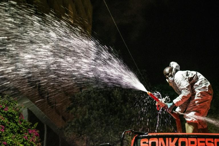 Kenyan firefighters sprayed disinfectant onto the streets during a nightly curfew (AFP Photo/Gordwin ODHIAMBO)
