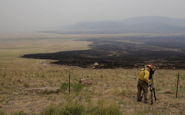 A videographer records the Valles Caldera National Preserve burned by the Las Conchas fire near Los Alamos, N.M., Saturday, July 2, 2011. With firefighters holding their ground against the largest wildfire ever in New Mexico, officials at the nation's premier nuclear weapons laboratory and in the surrounding city planned for the return of thousands of evacuated employees and residents. (AP Photo/Jae C. Hong)