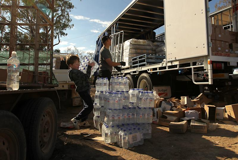 A local Mungindi boy lifts bottles of water our of a truck carrying food and water aid to the drought-stricken town. Source: AAP