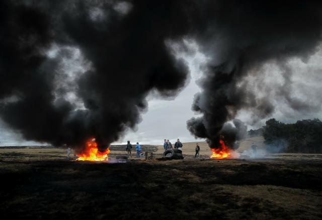 In this picture taken on Sunday, March 10, 2019, a children and youngsters stand by burning tires during a ritual marking the upcoming Clean Monday, the beginning of the Great Lent, 40 days ahead of Orthodox Easter, on the hills surrounding the village of Poplaca, in central Romania's Transylvania region. Romanian villagers burn piles of used tires then spin them in the Transylvanian hills in a ritual they believe will ward off evil spirits as they begin a period of 40 days of abstention, when Orthodox Christians cut out meat, fish, eggs, and dairy. (AP Photo/Vadim Ghirda)