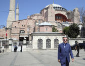 """Turkey's President Recep Tayyip Erdogan arrives to speak to supporters and the media after Friday prayers in Hagia Sophia, in the background, in Istanbul, Friday, Aug. 7, 2020. Erdogan joined worshipers on July 24 for the first Muslim prayers in 86 years inside the Istanbul landmark that served as one of Christendom's most significant cathedrals, a mosque and a museum before its conversion back into a Muslim place of worship.Turkey's president has called a maritime deal between Greece and Egypt """"worthless,"""" saying Turkey will resume oil and gas exploration in the Eastern Mediterranean.(Turkish Presidency via AP, Pool)"""