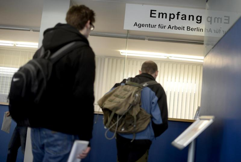 """Two job seekers stand in front of the reception at a unemployment centre """"Agentur fuer Arbeit"""" on April 11, 2012, at the district Kreuzberg in Berlin, Germany"""
