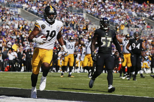 Pittsburgh Steelers wide receiver JuJu Smith-Schuster (19) carries the ball into the end zone for a touchdown as Baltimore Ravens inside linebacker C.J. Mosley (57) watches during the first half of an NFL football game in Baltimore, Sunday, Oct. 1, 2017. (AP)