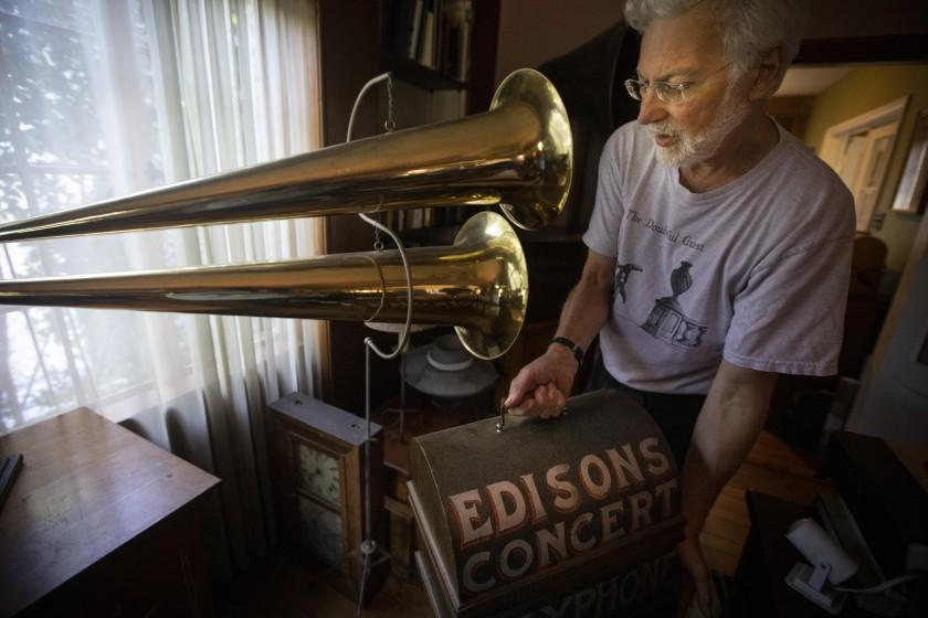 "SILVER LAKE, CALIF. - AUGUST 24, 2019: Collector John Levin of Silver Lake, Calif. show the Los Angeles Times some of his renowned wax cylinder at his home on Saturday, Aug. 24, 2019. According to Levin he is standing next to ""a 1900 double-horned phonograph used in the traveling media shows that were typical of the era. This machine easily filled a large tent with music."" (Francine Orr / Los Angeles Times)"
