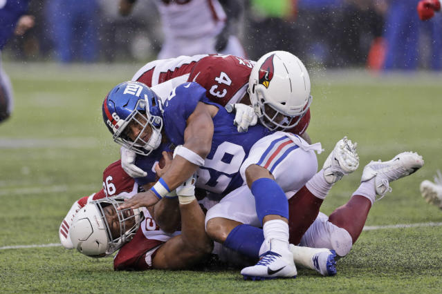 New York Giants' Saquon Barkley, center, is brought down by Arizona Cardinals defense during the second half of an NFL football game, Sunday, Oct. 20, 2019, in East Rutherford, N.J. (AP Photo/Adam Hunger)