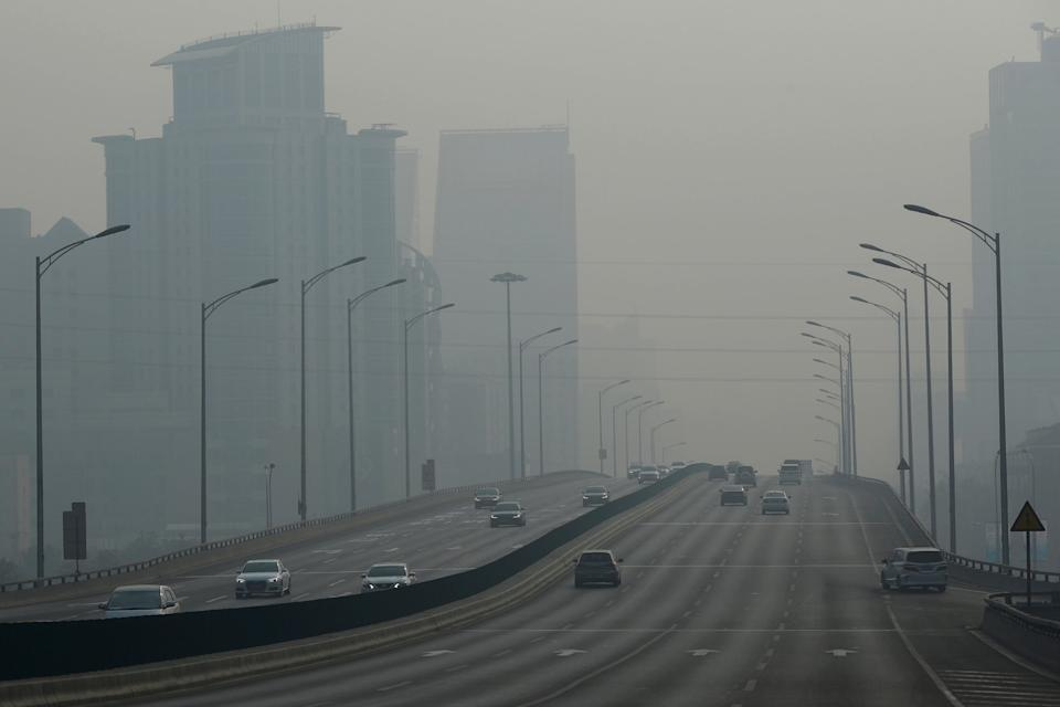 Vehicles travel on a main road as air pollution reduces visability in Beijing: EPA