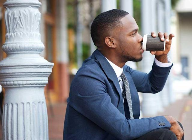 suited man drinking coffee