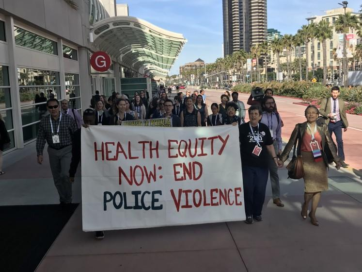 Attendees at a public health meeting protest police violence