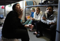 """Boshra al-Moallem, second left, sits in a room with her two sisters and brother-in-law at a refugee center in Bialystok, Poland, on Wednesday, Sept. 29, 2021. After enduring a decade of war in Syria, Boshra al-Moallem and her two sisters seized their chance to flee, but the journey proved terrifying and nearly deadly. Al-Moallem, originally from Homs but who displaced to Damascus by the war, is one of thousands of people who have traveled to Belarus in recent weeks and then found herself helped to cross the border with the help of Belarusian guards, something the EU considers a form of """"hybrid war"""" waged against the bloc with the use of human lives. (AP Photo/Czarek Sokolowski)"""