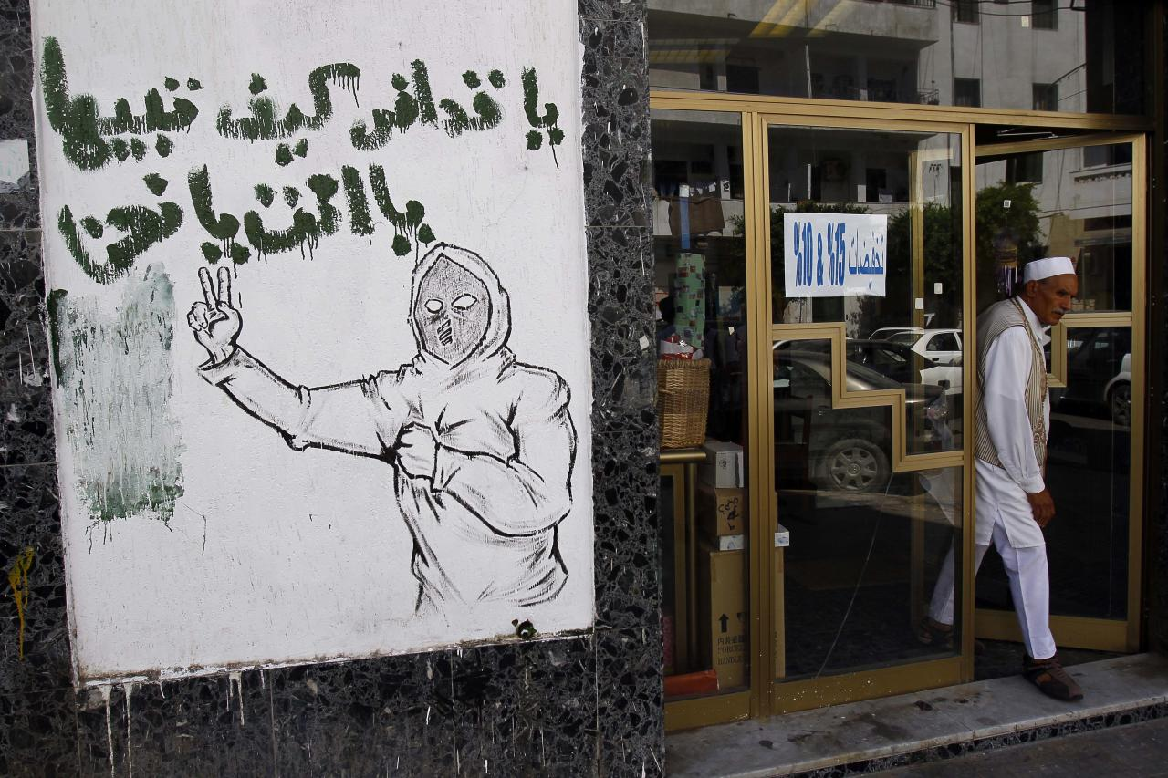 """A graffiti reading """"Hey Gadhafi, for Libya it is either you or US"""" is seen in the streets in Tripoli, Libya, Tuesday, Sept. 20, 2011. Libyan graffiti artists are taking advantage of newfound freedom to make fun of ousted leader Moammar Gadhafi on the streets of Tripoli, after 42-years of authoritarian rule artists are able to express themselves in public spaces.(AP Photo/Francois Mori)"""