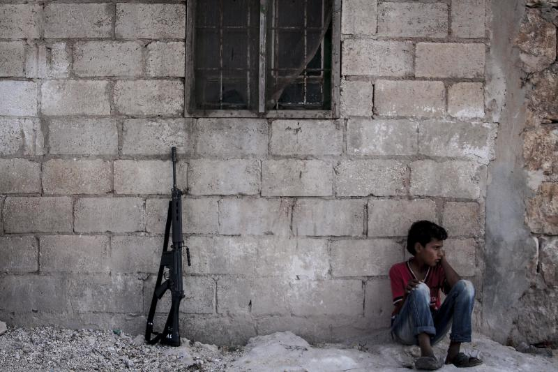 In this Thursday, Sept. 19, 2013 photo, a Syrian child sits on the ground next to an opposition fighter's weapon in the Idlib province countryside, Syria. For Syria's divided and beleaguered rebels, the creeping realization that there will not be a decisive Western military intervention on their behalf is a huge psychological blow. It now appears that the regime of Bashar Assad has gained time, largely because the world community is too concerned that if he is toppled the result may be an Islamist Syria in the grip of al-Qaida. The immediate result, this week, has been an uptick in infighting between moderate and jihadi rebels.(AP Photo)
