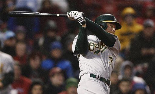 Oakland Athletics' Brandon Moss follows through on a two-run single during the third inning of a baseball game against the Boston Red Sox at Fenway Park in Boston, Tuesday, April 23, 2013. (AP Photo/Winslow Townson)