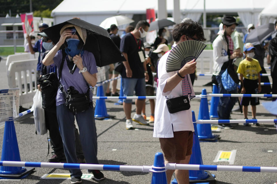 Visitors use fans and umbrellas in the heat outside the Fuji International Speedway, the finish for the women's cycling road race that is underway, at the 2020 Summer Olympics, Sunday, July 25, 2021, in Oyama, Japan. (AP Photo/Christophe Ena)