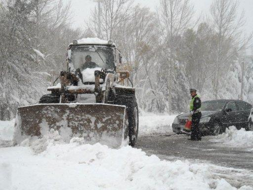 A worker uses a bulldozer to clear a snow-covered street after heavy snow-fall in the outskirts of Beijing on November 4