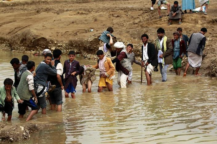 Yemenis cross a flooded road following heavy rain fall, in the city of Amran, 50 kms north of Sanaa, on April 15, 2016 (AFP Photo/Mohammed Huwais)
