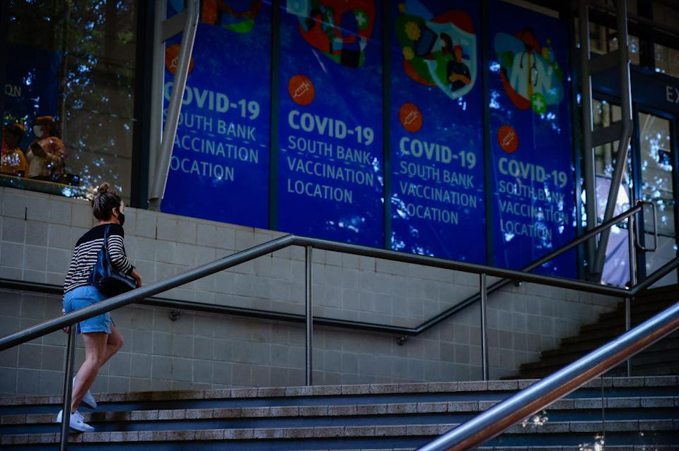 A woman walk past signage at a Covid-19 vaccination hub at the Brisbane Convention and Exhibition Centre in Brisbane.