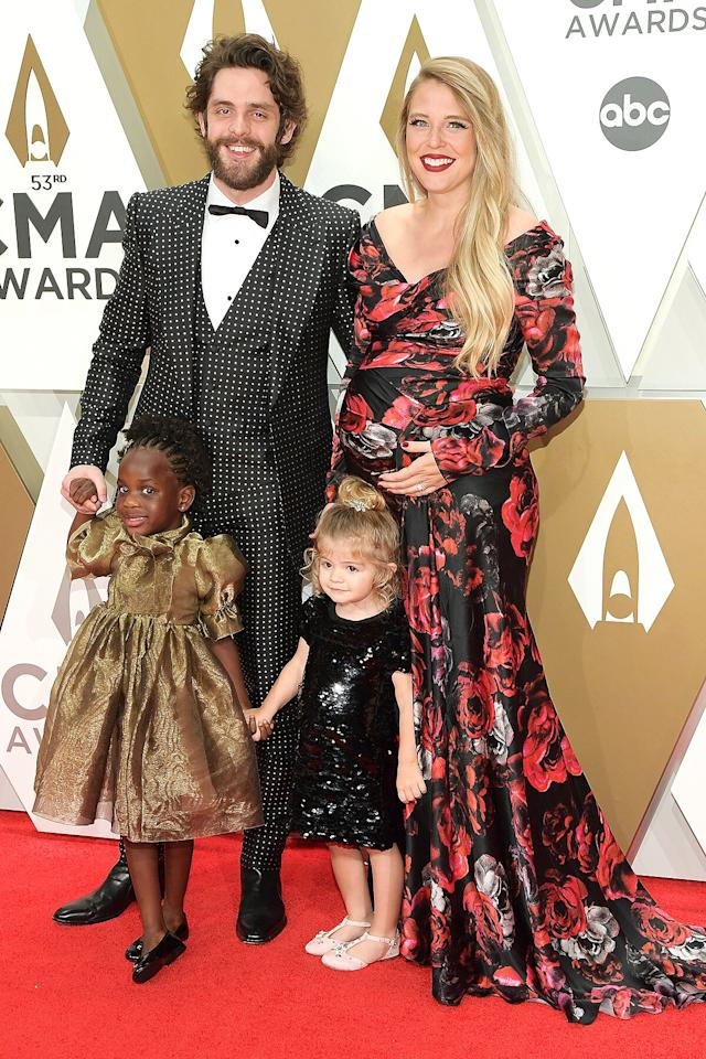 """The country star and his wife, pictured with their daughters Ada James and Willa Gray, <a href=""""https://people.com/parents/cmas-2019-thomas-rhett-lauren-akins-pregnant-daughters-red-carpet/"""">are expecting another girl in early February</a>."""