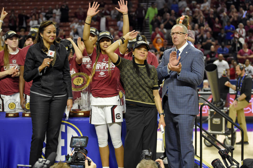 South Carolina head coach Dawn Staley, center right, and Tyasha Harris, center left, acknowledge the crowd after defeating Mississippi State in a championship match at the Southeastern Conference women's NCAA college basketball tournament in Greenville, S.C., Sunday, March 8, 2020. (AP Photo/Richard Shiro)