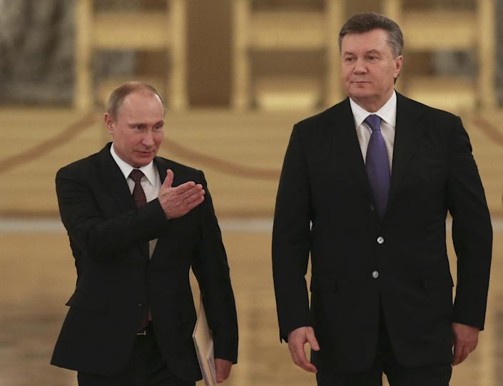 """FILE - In this Tuesday, Dec. 17, 2013 file photo Russian President Vladimir Putin, left, shows the way to his Ukrainian counterpart Viktor Yanukovych during a meeting in the Kremlin in Moscow, Russia. Moscow on Wednesday granted Ukrainian President Viktor Yanukovych protection """"on the territory of Russia,"""" shortly after the fugitive leader sought help from the Kremlin, according to an official quoted by Russian news agencies. (AP Photo/Sergei Karpukhin, Pool, file)"""