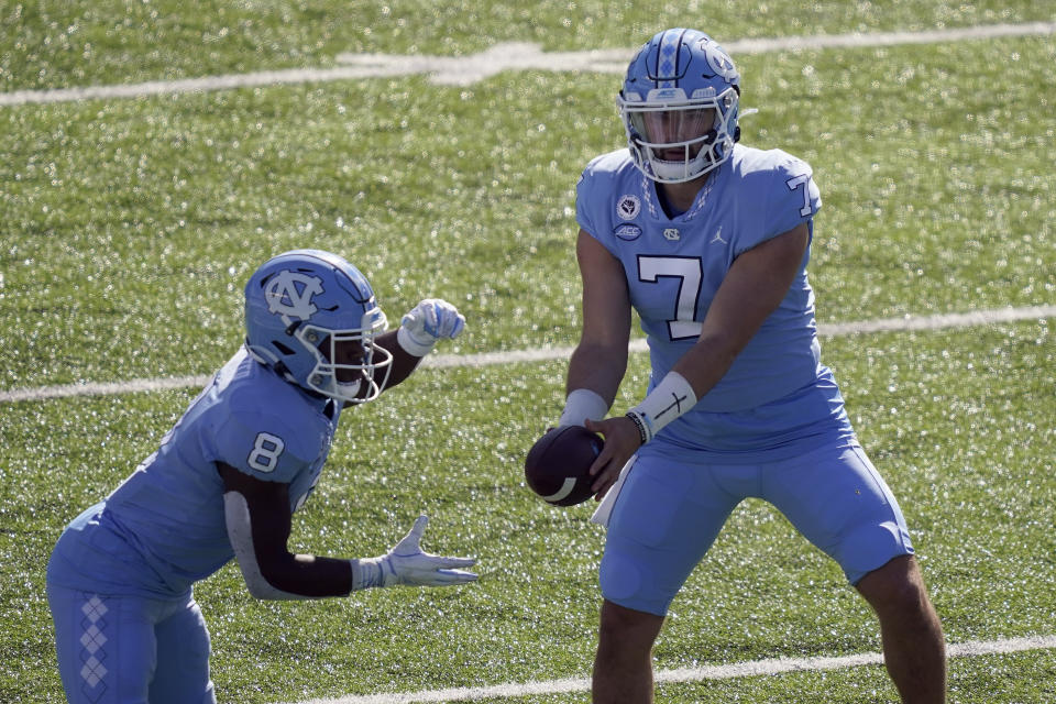 North Carolina quarterback Sam Howell (7) hands off the ball to running back Michael Carter (8) during the first half of an NCAA college football game against North Carolina State in Chapel Hill, N.C., Saturday, Oct. 24, 2020. (AP Photo/Gerry Broome)