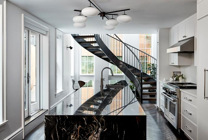 "<div class=""caption""> In the fully renovated garden-level kitchen, an island in black belvedere granite takes center stage. The flush-mounted fixture is an Angelo Lelli six-arm design from <a href=""https://carlylecollective.com"" rel=""nofollow noopener"" target=""_blank"" data-ylk=""slk:Carlyle Collective"" class=""link rapid-noclick-resp"">Carlyle Collective</a>. </div>"