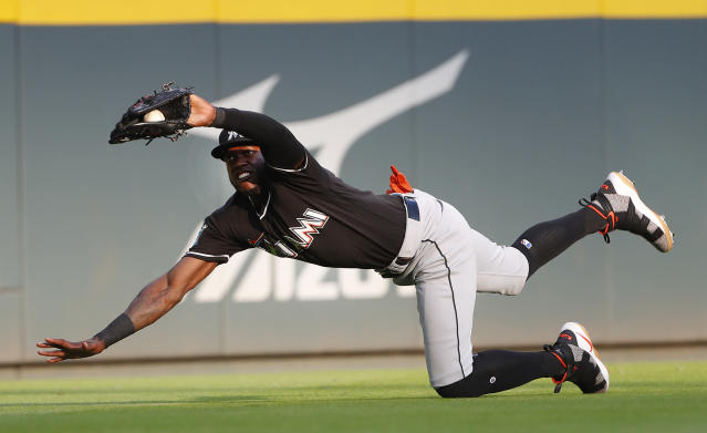 Miami Marlins left fielder Cameron Maybin (1) makes a diving catch for the out on Atlanta Braves' Ozzie Albies duirng the first inning of a baseball game Saturday, May 19, 2018, in Atlanta. (AP Photo/John Bazemore)