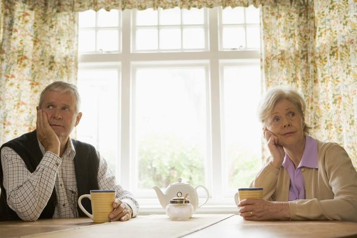 Unhappy senior couple sitting at a table