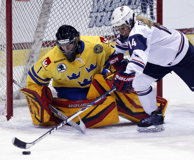 United States' Brianna Decker (14) chases the puck in front of Sweden goalie Sara Grahn (1) during the first period of the Four Nations Cup women's third-place hockey game Saturday, Nov. 9, 2013, in Lake Placid, N.Y. (AP Photo/Mike Groll)