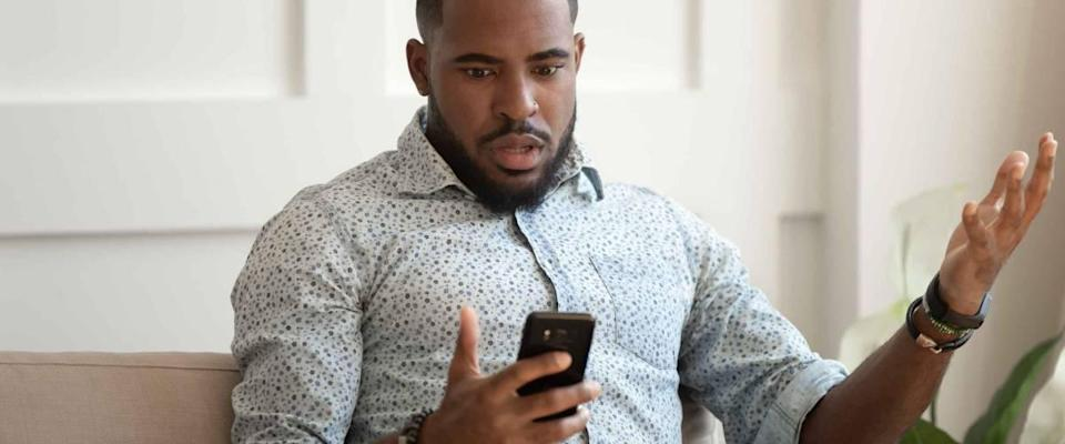 African astonished man sitting on sofa holds cellphone