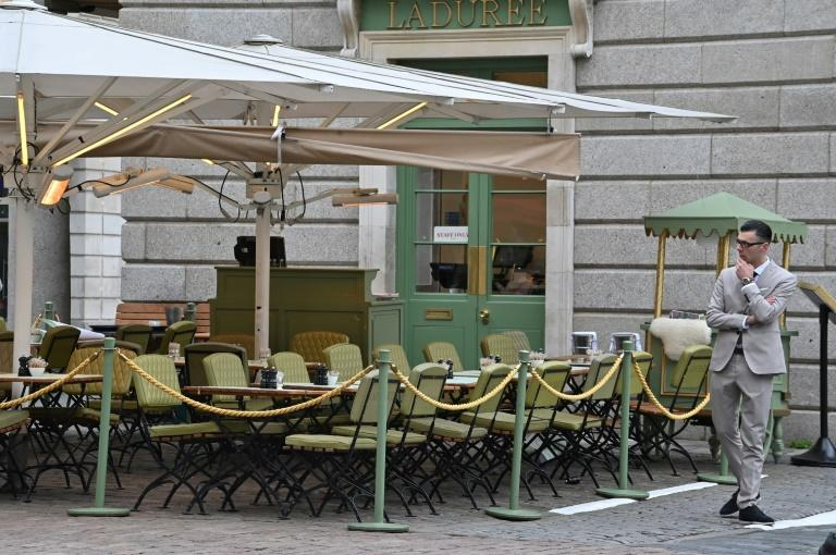A restaurant employee stands by empty tables in a quiet Covent Garden in central London on March 17, 2020 after the UK government announced stringent social distancing advice
