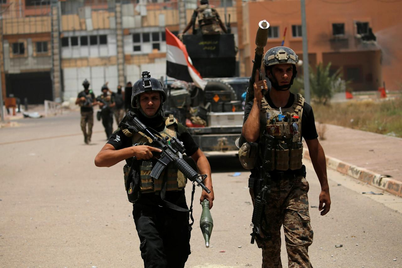 <p>Iraqi security forces walk with their weapons at a hospital in Fallujah, Iraq. (Photo: Thaier Al-Sudani/Reuters) </p>