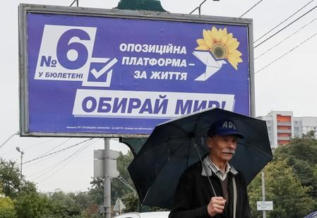 A man walks past an election campaign poster of Ukrainian Opposition Platform - For Life political party in Kiev
