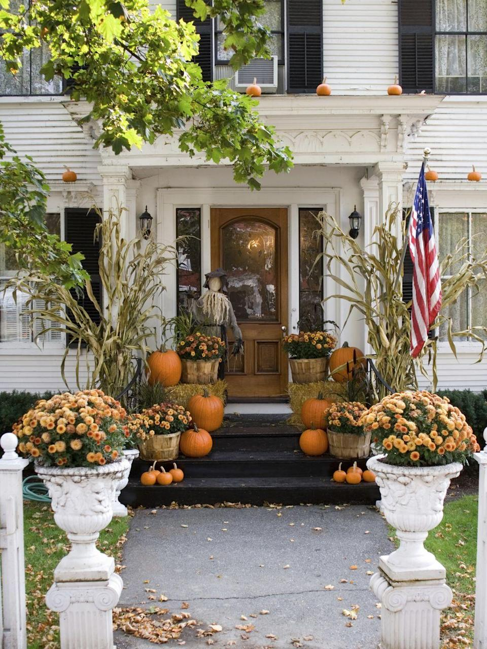 <p>Don't confine pumpkins to the ground: If your porch has a stable overhang, like the one pictured here, use a ladder to elevate your display by placing a few mini pumpkins overhead. </p>