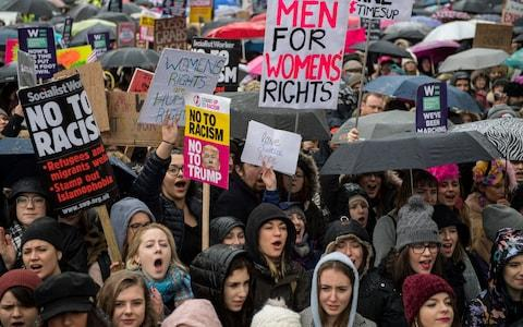 Women's rights demonstrators hold placards and chant slogans during the Time's Up rally  - Credit: Getty
